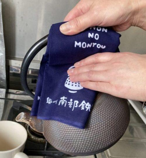 手拭いを使って鉄瓶を持つ